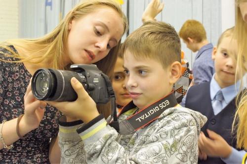 девушка показывает ребенку как пользоваться камерой