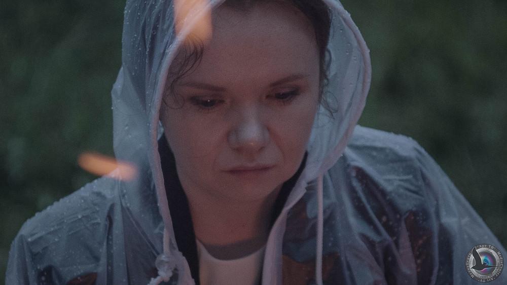 женщина в дождевике сидит у костра, разлетаются искры