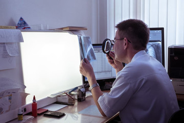 врач рентгенолог смотрит через лупу на снимок