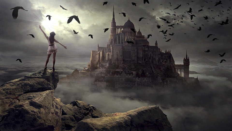 Image of girl standing on the edge of cliff with a castle in the background.