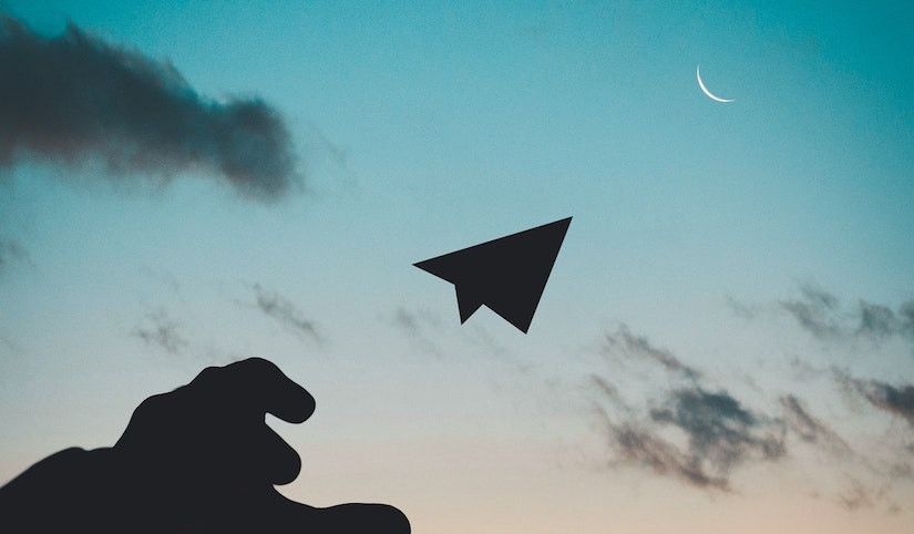 Silhouette of a hand and paper airplane with a sky background