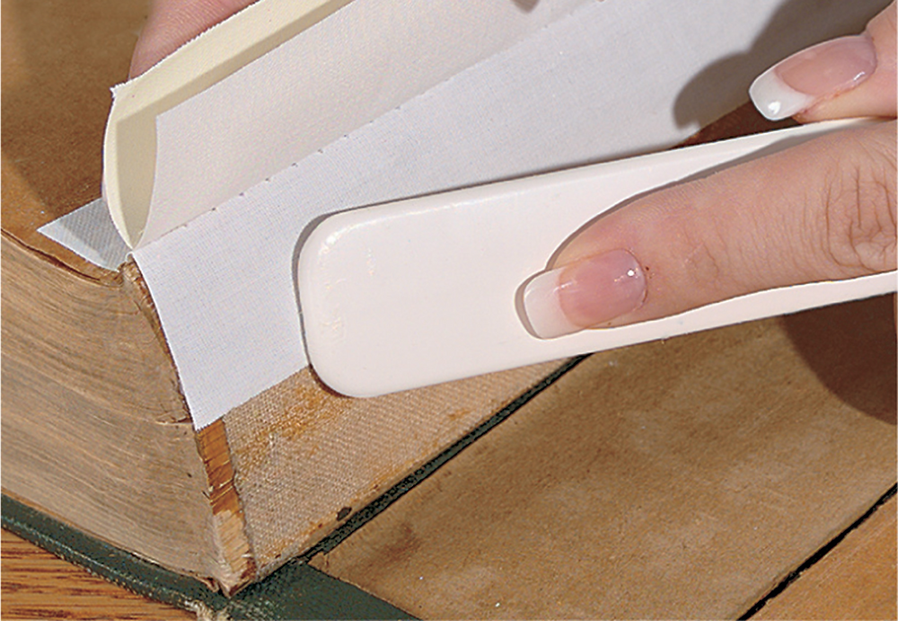 A mending bone being used to secure a book spine