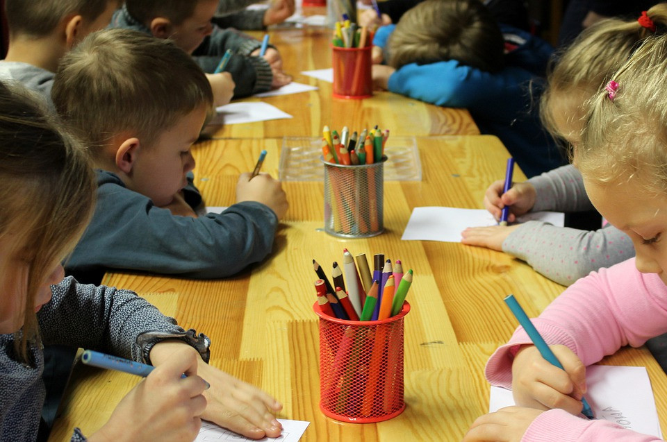 Kids sitting at a long row of tables coloring with colored pencils
