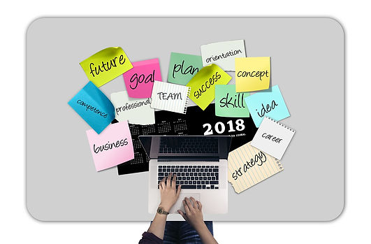 """Open laptop surrounded by post-it notes with text with words such as """"future"""" """"goal"""" """"business"""" et cetera"""
