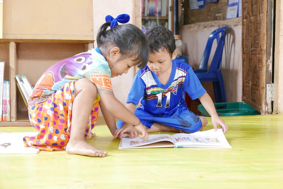Young boy and girl looking at a book on the floor