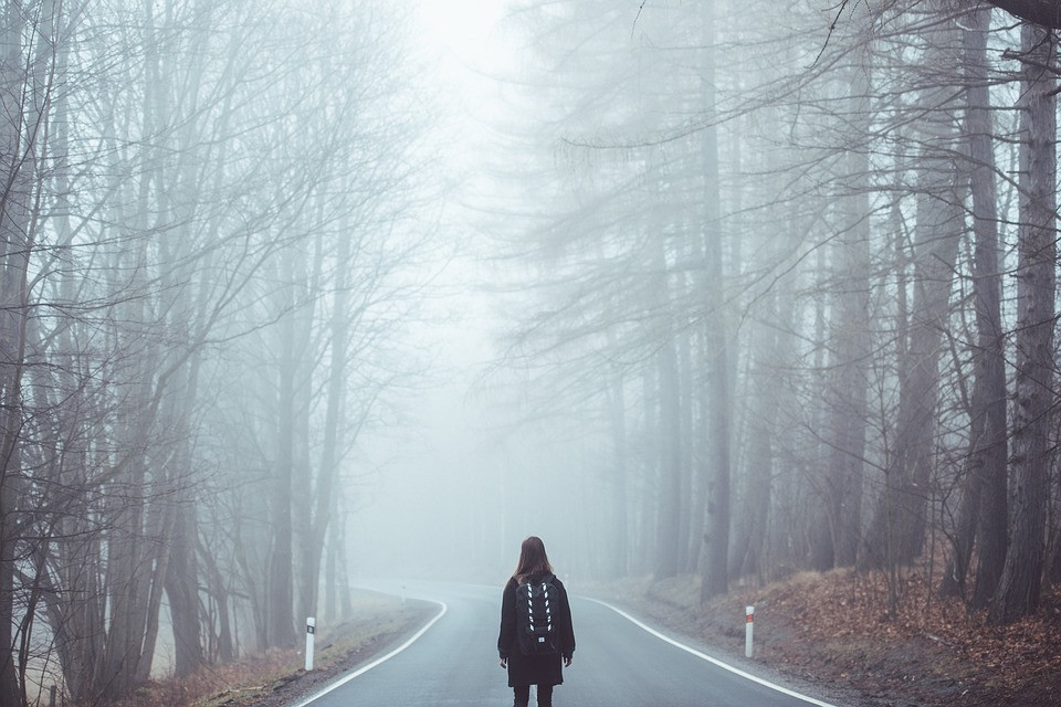 A girl stands in the middle of a road facing a foggy forest.