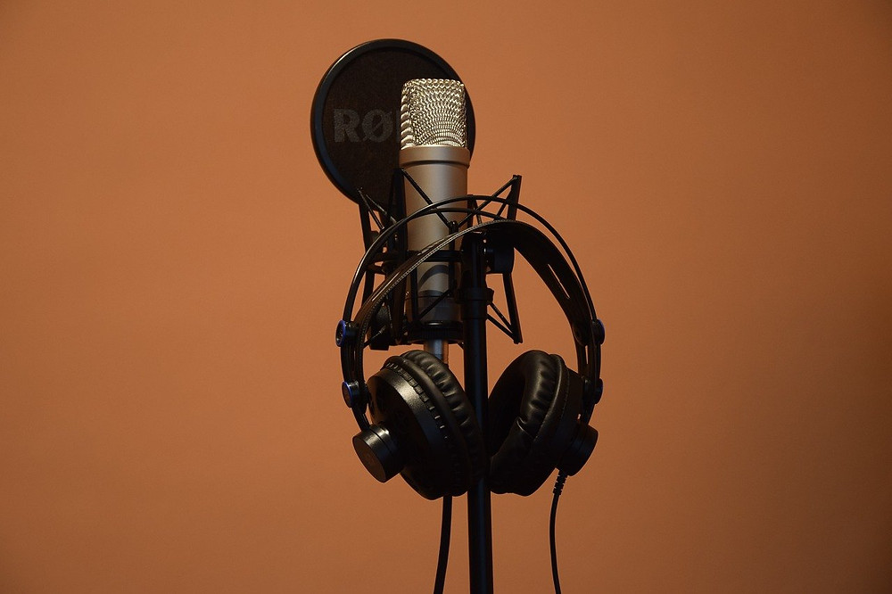 pop filter, microphone, and headphones on a microphone stand