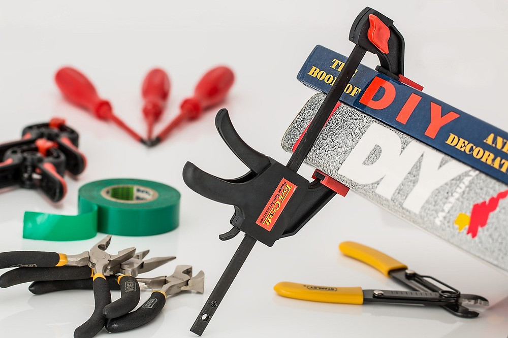 Variety of tools on a white table, clamp is hold two DIY books together