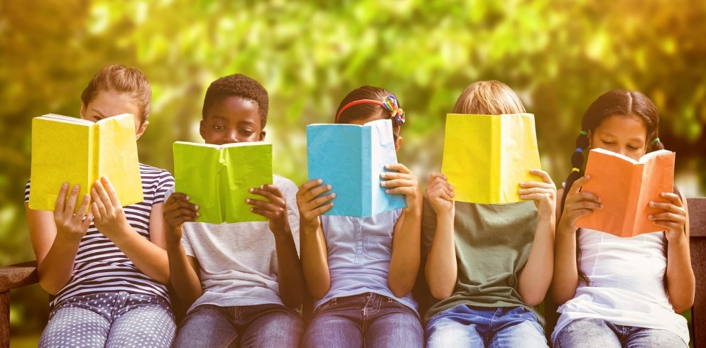 Five kids sitting on a bench holding books in front of their faces