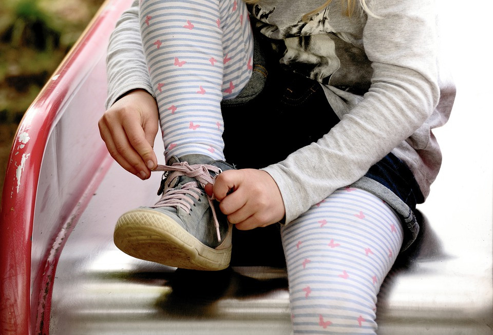 Young child tying her shoes