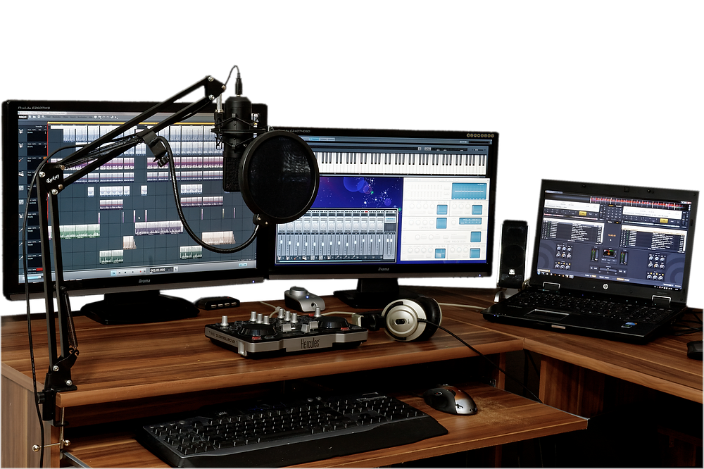 desktop recording set up - two monitors, a laptop, pop filter and microphone on a desktop