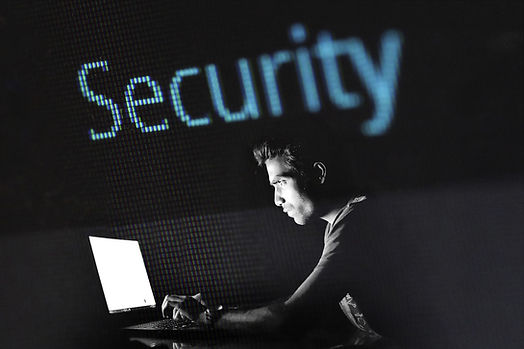 """Man sitting at a laptop in a dark room, with the word """"security"""" in blue pixelated text across the background"""
