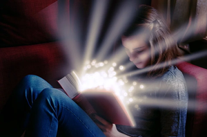 Girl sitting reading a book with light coming out of it.