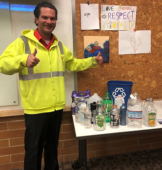 "Man in bright yellow construction jacket makes ""thumbs up"" gesture in front of a table of recyclable items."
