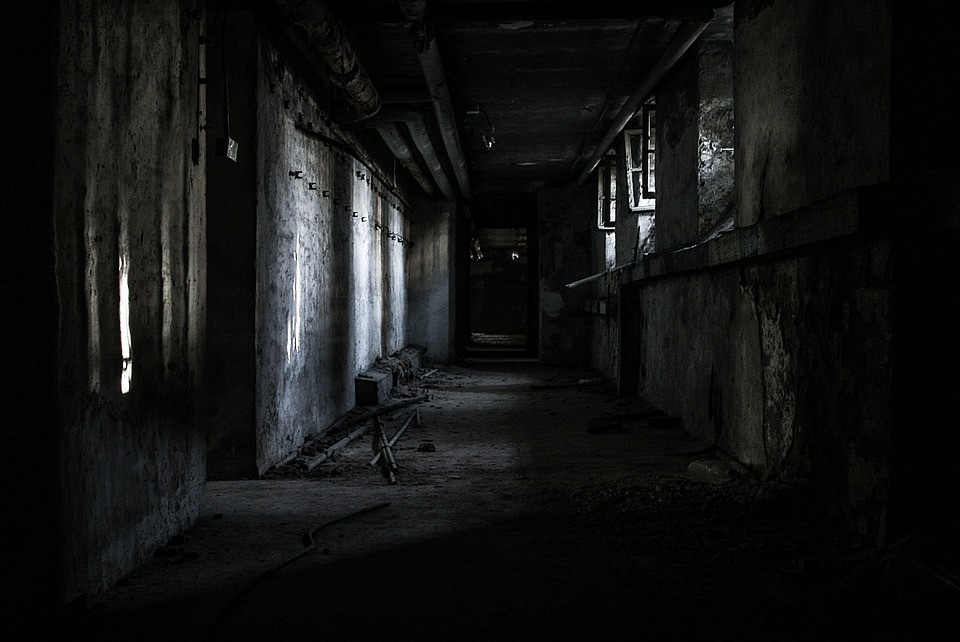 a dark hallway in an abandoned building