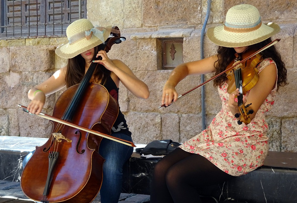 Photo of two women wearing hats and sitting, one playing a cello and the other a violin