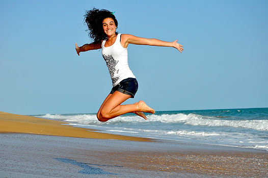 Woman jumping in air with arms outspread at a beach.