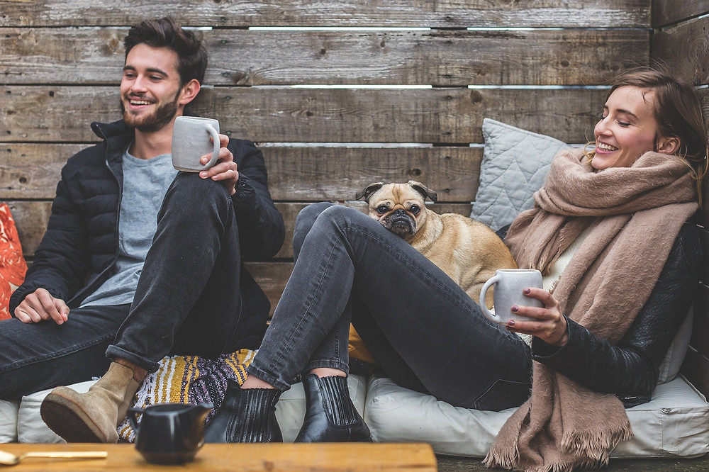 Photo of man and woman with coffee mugs sitting on a couch smiling. There is a pug on the woman's lap.