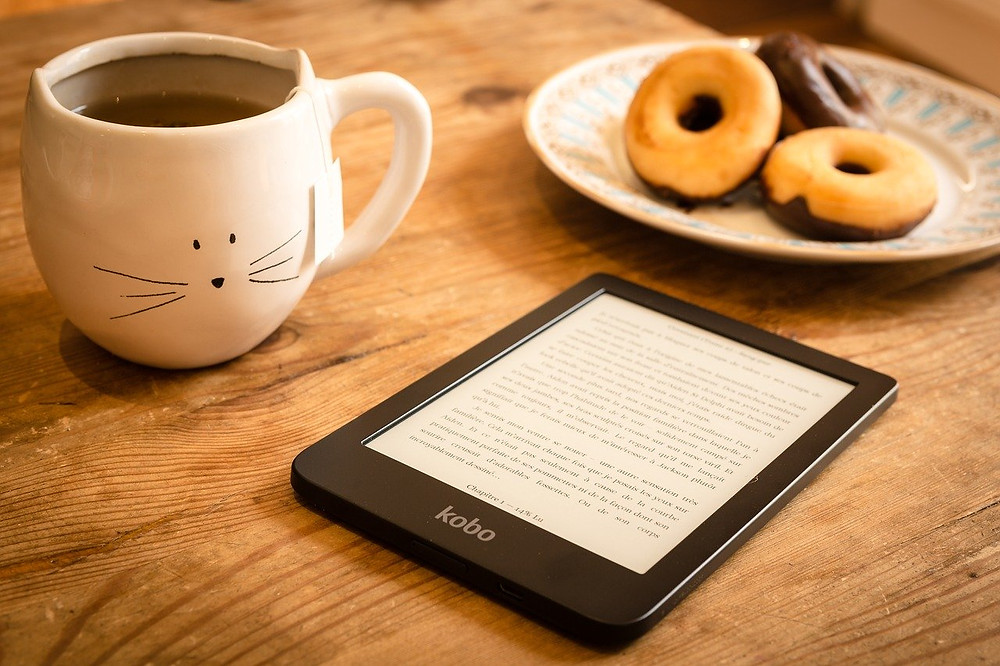 Table setting of a Kobo reader, plate of donuts, and cat mug with tea