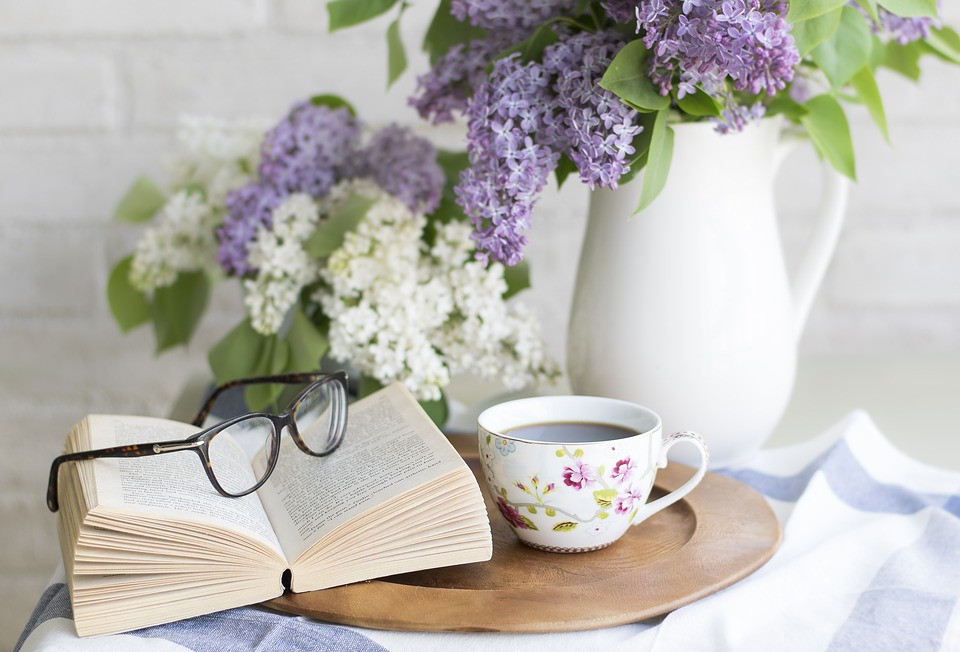Photo of a small table with an open book, cup of coffee, purple flowers, and eyeglasses.