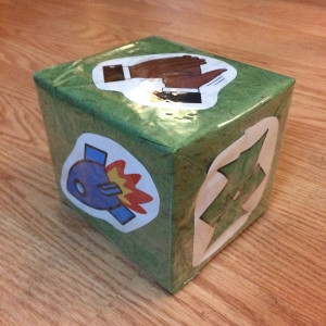 the side of a square box wrapped in green paper with an image stuck to each side of the box