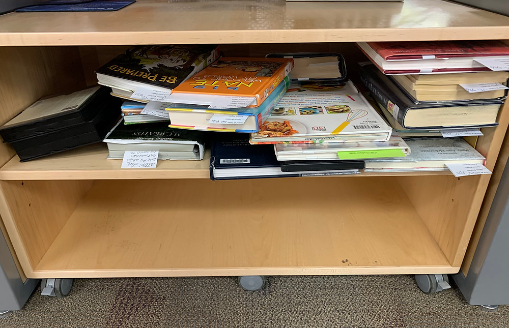 Books on a shelf waiting to go through repair/mending