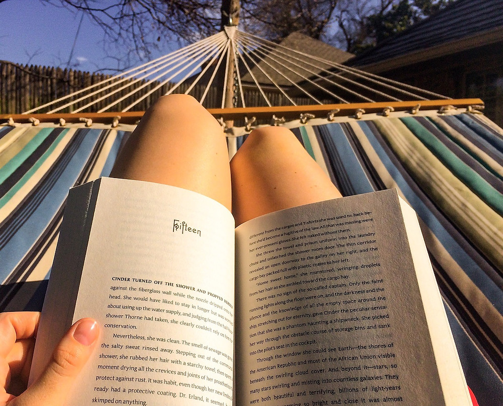 Photo of person holding book on their lap in a hammock
