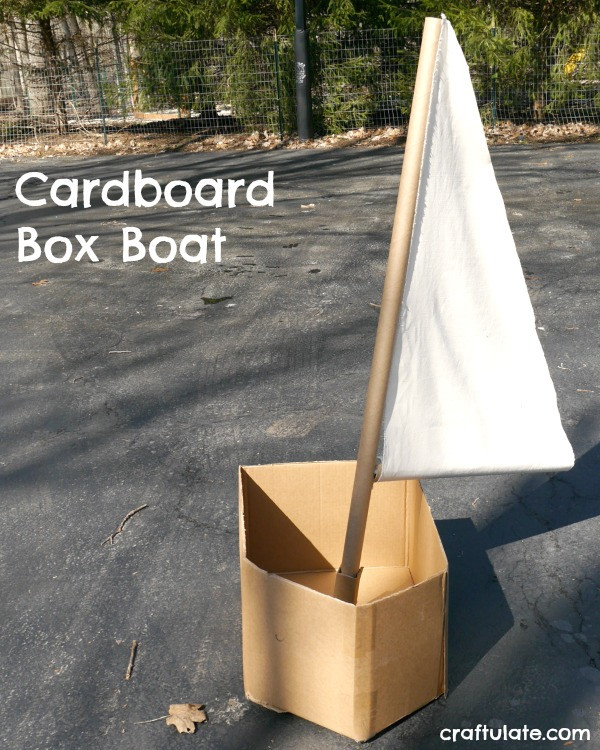 A cardboard box made into a boat with a cardboard and cloth sail