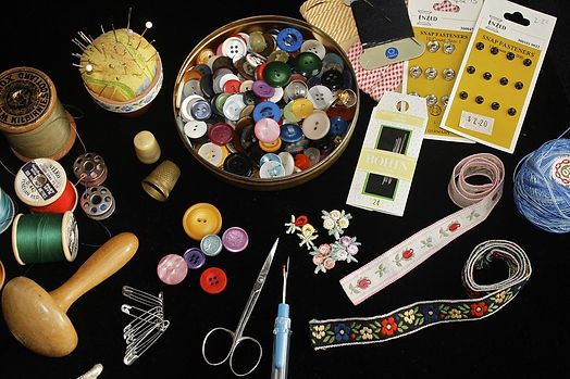 Buttons, snaps, floral ribbons, and needles and thread arranged on a black background.