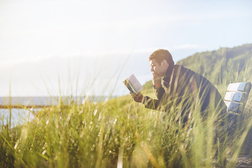 Man reading a book and sitting on a bench in a field of wild grass with the ocean in the backgroun