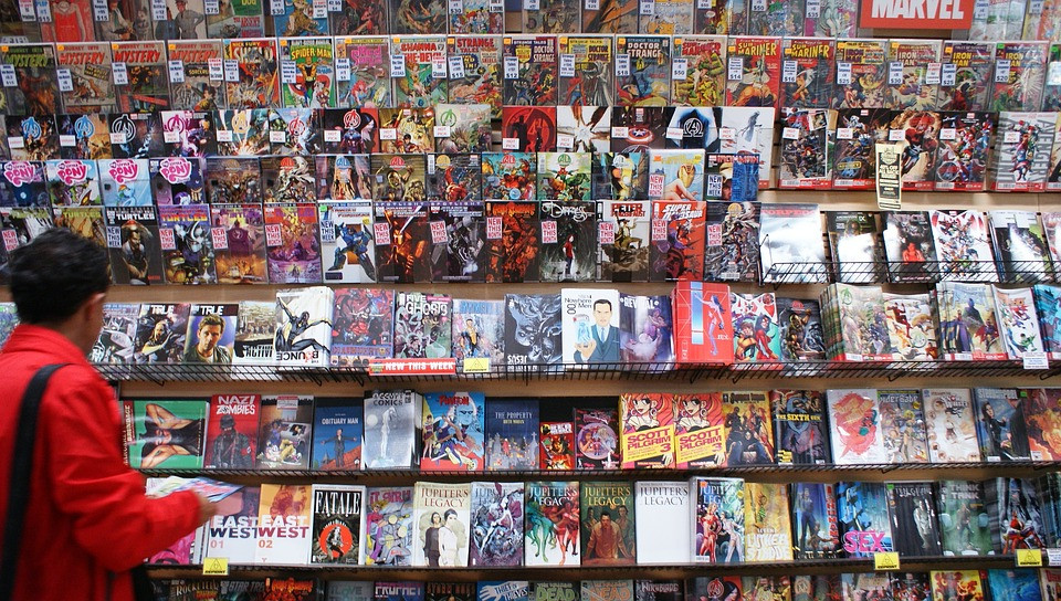 Woman in red jacket in front of a wall of comic book shelves and hundreds of comic books.