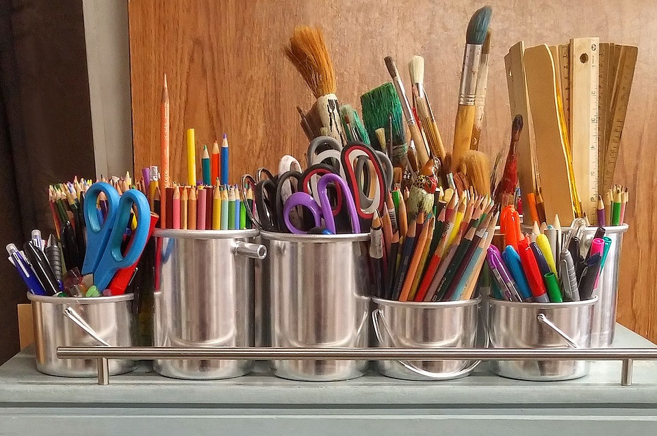 Art supplies - pencils, colored pencils, scissors, pens, rulers, markers, and paintbrushes in aluminum cans on a table