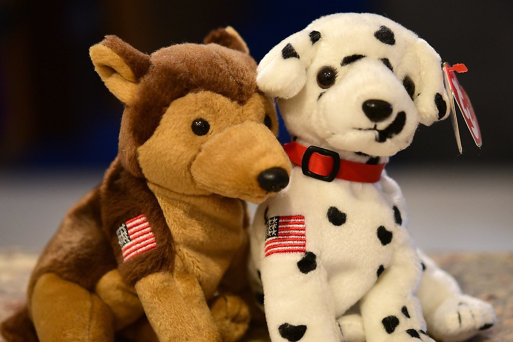 Brown dog and dalmatian dog beanie babies with American flags on their upper forearms