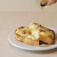 チーズトースト   こだわりの山食にたっぷりのミックスチーズ、ゴルゴンゾーラ、クルミを散らして焼き上げブラックペッパーとメープルシロップで仕上げています。  PLATE Brand:ALESSI PlateBowlCup Designer:Jasper Morrison