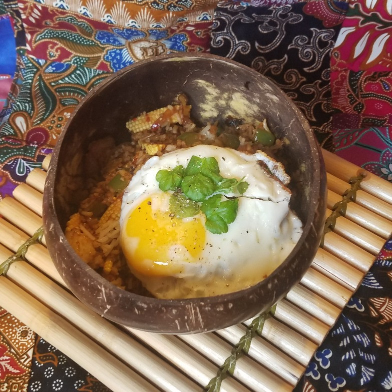 sambal fried rice with egg in coconut bowl and malaysian batik