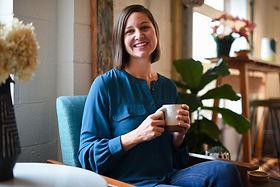 Meg Proctor, smiling, with coffee mug