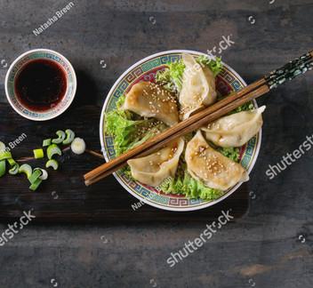 stock-photo-gyozas-potstickers-on-lettuc