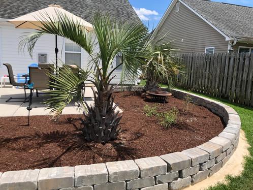Block wall installation around patio and palms