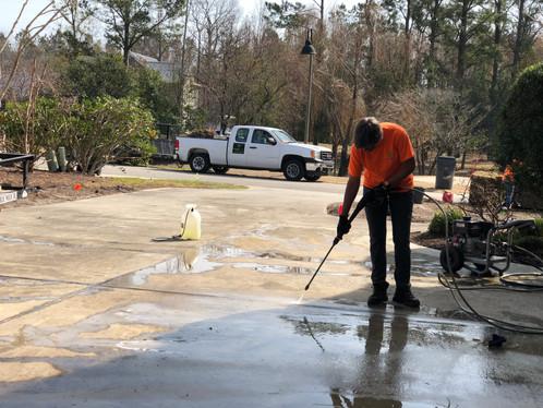 Pressure washing the driveway.