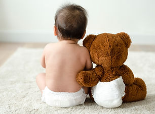 Back of a baby with a teddy bear.jpg