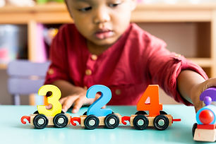 Little boy playing mathematics wooden to