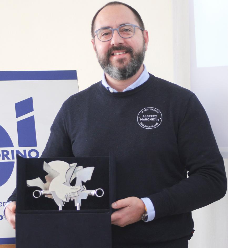 """Vincitore 2020 Categoria """"PICCOLA IMPRESA""""  ALBERTO MARCHETTI & C. S.r.l.  Alberto Marchetti & C. S.r.l. è una gelateria torinese, guidata dall'omonimo imprenditore, con una spiccata visione imprenditoriale e una scrupolosa attenzione per le materie prime. Nel corso del 2020, l'Azienda (che è già stata riconosciuta dalla Camera di commercio Maestro del Gusto di Torino e provincia), ha dimostrato una sorprendente capacità di adattamento al nuovo contesto, mettendo rapidamente in campo una serie di iniziative rivolte sia ai clienti sia ai propri dipendenti. L'utilizzo delle tecnologie digitali (campagne mediatiche sui social network e ricorso a piattaforme di delivery), ha permesso di offrire nuovi servizi come """"Vaschetta sorpresa"""" e """"Mantecato e Mangiato"""", dando ai clienti la possibilità di trascorrere un'ora in compagnia di Alberto Marchetti, mentre prepara il gelato in diretta streaming."""