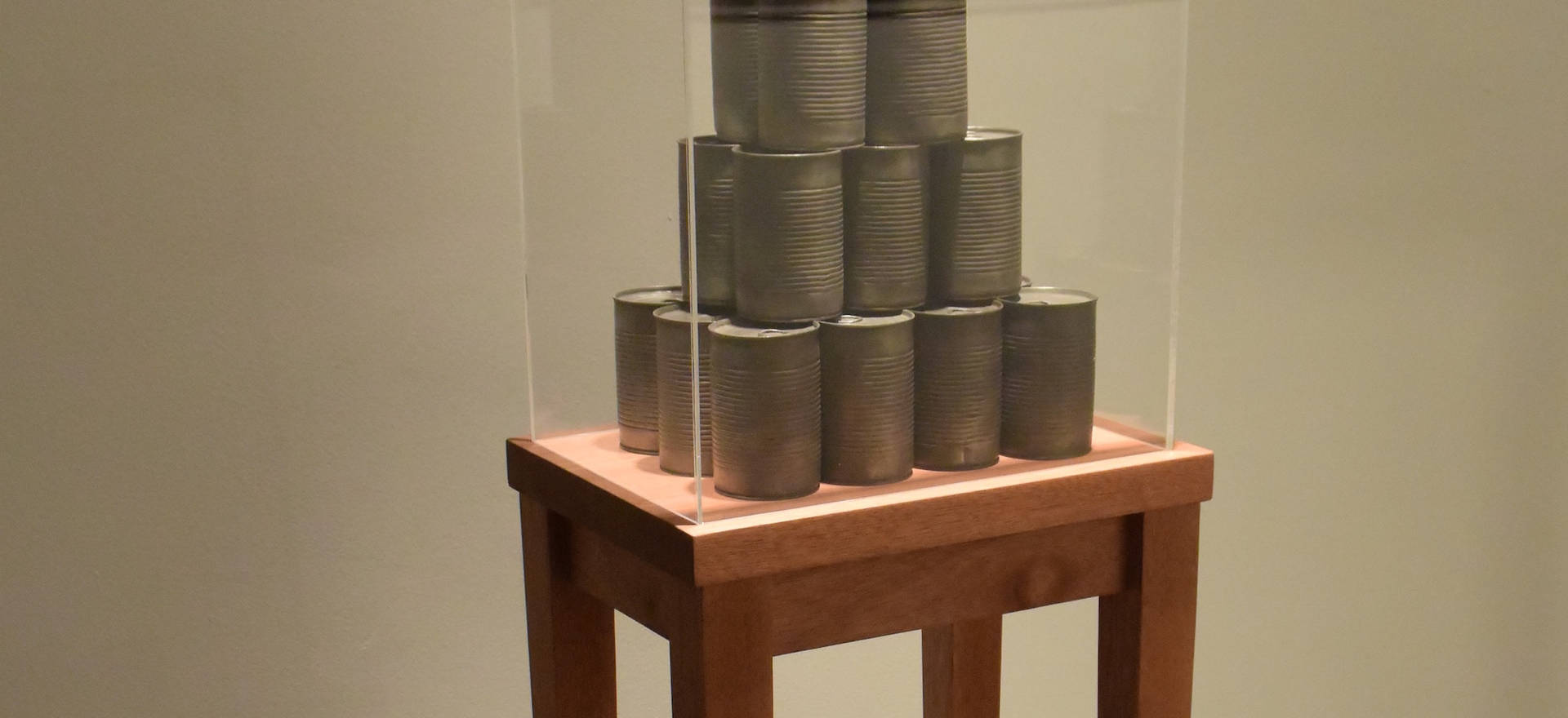 Timeless state of food III, 2014 Wood table with 25 reproductions in bronze of food cans and acrylic cover. 51.18 x 15.74 x 11.81 inches. 130 x 40 x 30 cm.