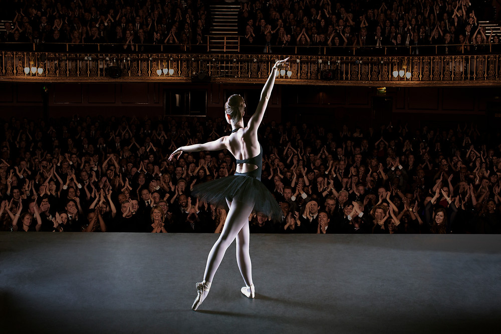 Dancer posing onstage in front of clapping audience