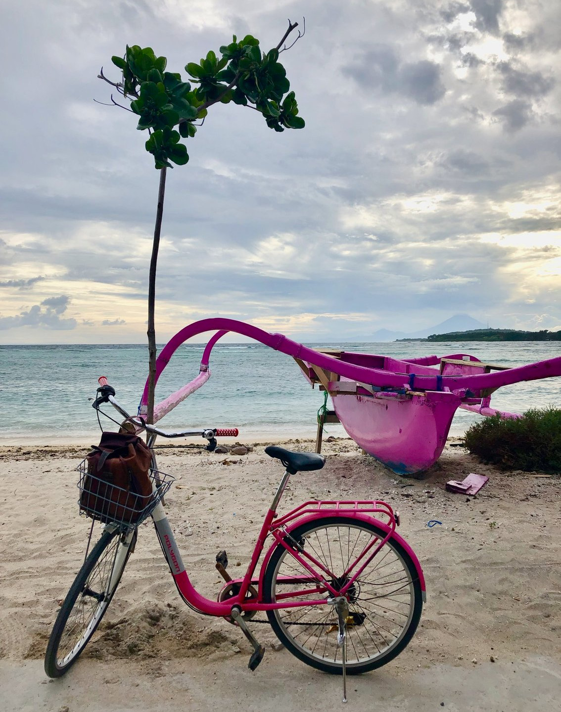Pink bicycle in front of pink boat at the beach