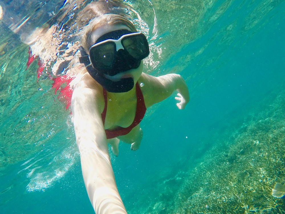 Girl snorkelling and filming with GoPro camera