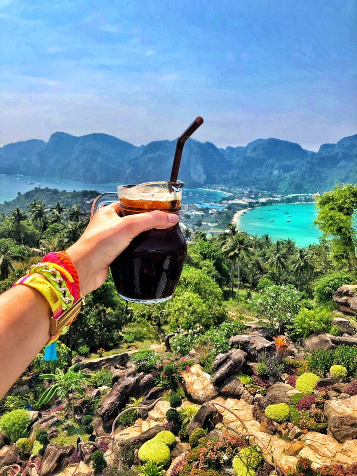 Holding Iced Coffee with view over tropical island
