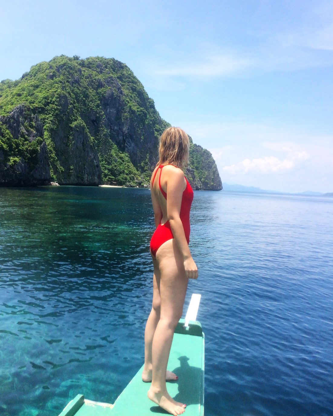 Girl in red swimsuit standing in the front of a boat looking over the ocean