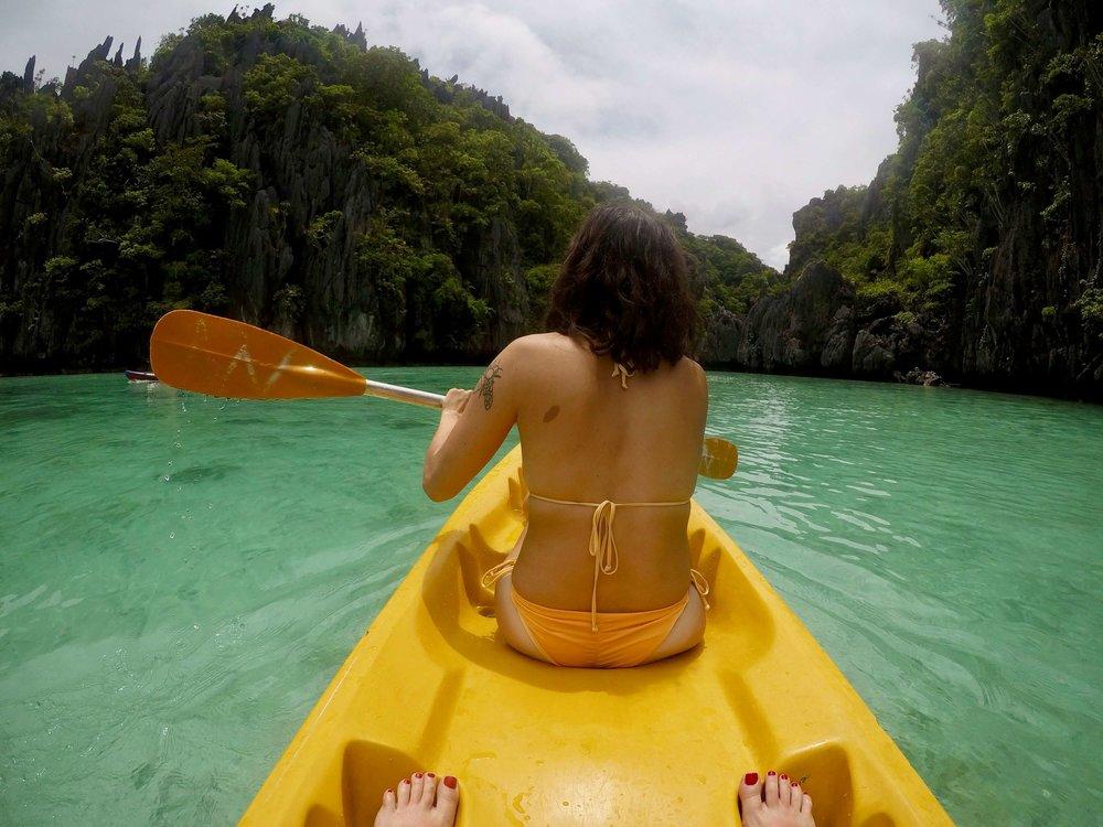 Girl holding paddle while kayaking through a lagoon