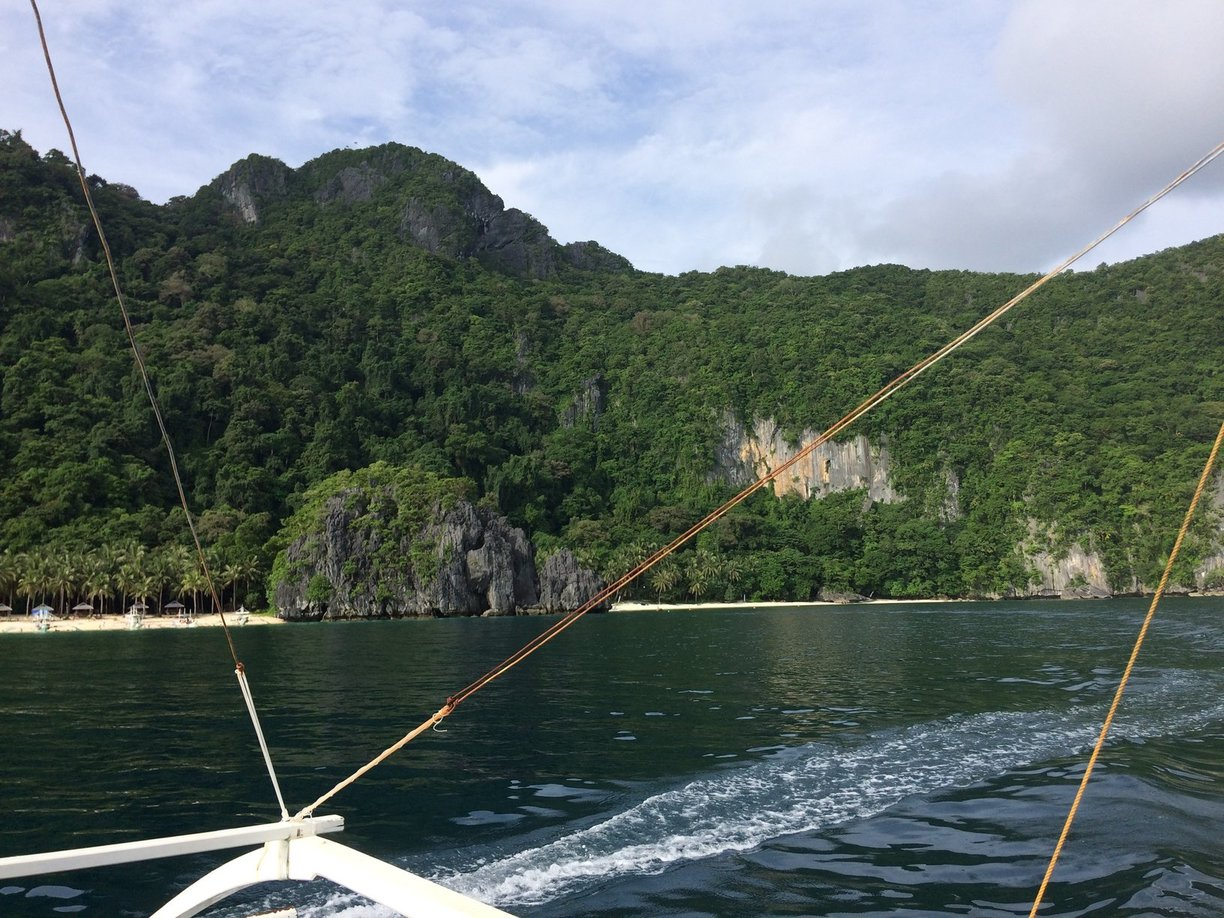 On a boat in the ocean with mountain in the background